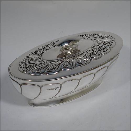An Antique Edwardian Sterling Silver pot pourri holder, having an oval body with hand-chased fluted decoration, a lift-off lid with a cast oval handle and hand-pierced floral and scroll work, all sitting on an oval collet foot. Made by Walker and Hall of Sheffield in 1908. The dimensions of this fine hand-made antique silver pot-pourri holder are length 16 cms (6.5 inches), width height 9 cms (3.5 inches), height 7 cms (2.75 inches), and it weighs approx. 308g (10 troy ounces)