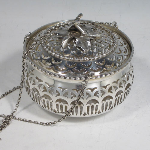 Antique Edwardian sterling silver pot pourri holder, having a round bellied hand-pierced body, a pull-off lid with cast floral finial, and an attached triple chain and hook. Made by Skinner and Co., of London in 1910. The dimensions of this fine hand-made silver pot-pourri holder are diameter 10 cms (4 inches), height 8.5 cms (3.25 inches), and it weighs approx. 204g (6.6 troy ounces).