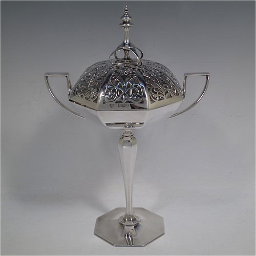 A very handsome and large Antique Edwardian Sterling Silver pot pourri holder in an Art Nouveau style, having an unusual trophy shaped body with two-side-handles, a lift off hand-pierced and panelled lid with cast urn-shaped finial, and all sitting on an octagonal pedestal foot. Made by Goldsmiths and Silversmiths of London in 1907. The dimensions of this fine hand-made antique silver pot-pourri holder are height  28 cms (11 inches), spread across arms 18.5 cms (7.25 inches), and it weighs approx. 482g (15.5 troy ounces)