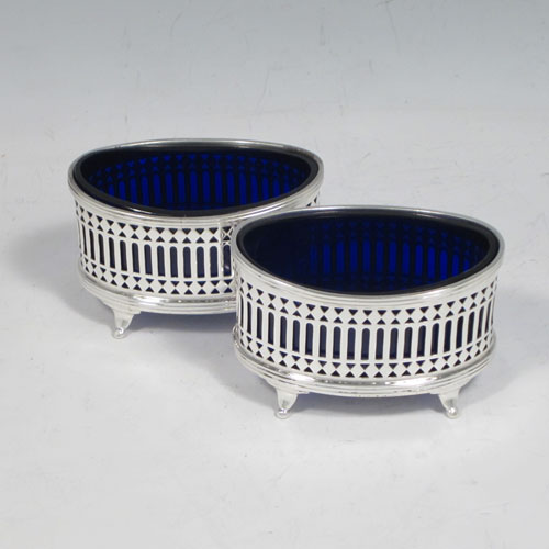 Sterling silver pair of salt cellars, having oval boat-shaped bodies with hand-pierced galleried sides, applied reed-edged borders, original blue-glass liners, and sitting on four flange feet. Made by Stokes and Ireland of Chester in 1913. The dimensions of this fine pair of silver salt cellars are length 7 cms (2.75 inches), height 4.5 cms (1.75 inches), width 4 cms (1.5 inches), and they weigh approx. 81g (2.6 troy ounces).