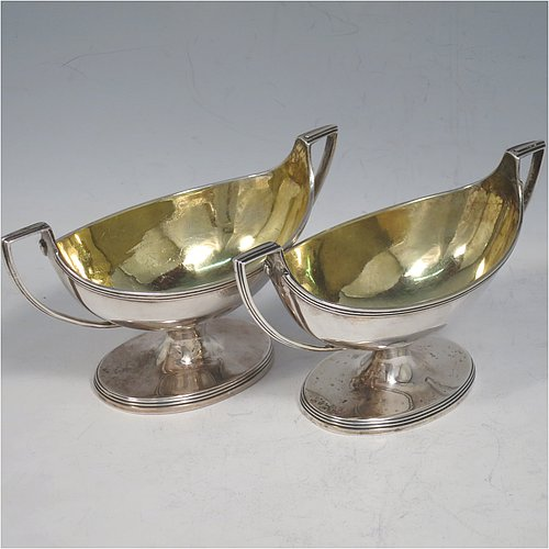 An Antique Georgian Sterling Silver pair of salt cellars, in a boat-shaped style, having plain oval bodies, with gold-gilt interiors, applied reeded borders, and reeded side-handles, all sitting on pedestal feet. Made by either Henry Nutting OR Hannah Northcote of London in 1803. The dimensions of these fine hand-made antique silver salt cellars are length 14 cms (5.5 inches), width 6 cms (2.3 inches), height 7.5 cms (3 inches), and they weigh a total of approx. 217g (7 troy ounces).
