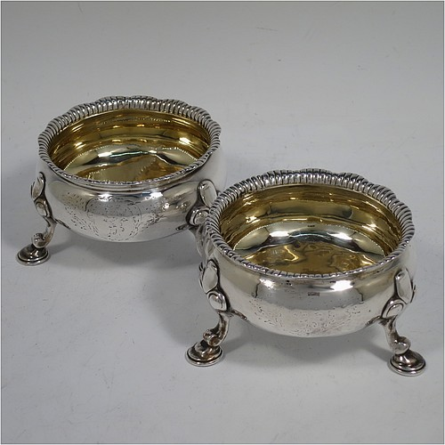 A large and handsome pair of Antique Georgian Sterling Silver salt cellars, having plain round bodies, with gold-gilt interiors, applied shaped gadroon borders, and all sitting on three cast hoof feet with foliate shoulders. Made by Peter Taylor of London in 1750. The dimensions of these fine hand-made antique silver salt cellars are diameter 8 cms (3 inches), height 5 cms (2 inches), and they weigh a total of approx. 224g (7.2 troy ounces). Please note that these items are crested.