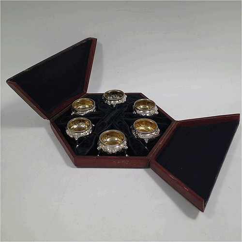 A very pretty set of six Antique Victorian Sterling Silver salt cellars, having round bellied  bodies with hand-chased floral decoration, bead-edged borders, gold-gilt interiors, and sitting on three cast hoof feet, all in there original blue velvet-lined presentation box. Made by Alexander Macrae of London in 1862. The dimensions of these fine hand-made antique silver salt cellars are diameter 4.5 cms (1.75 inches), height 3 cms (1.25 inches), and they weigh a total of approx. 212g (6.8 troy ounces).