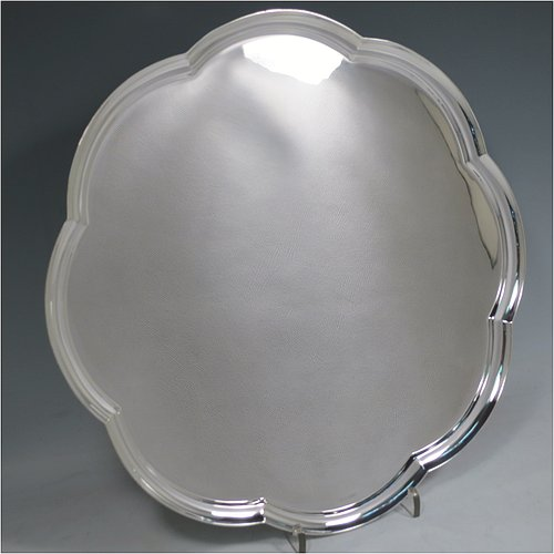 A Sterling Silver salver, having an applied Octafoil raised border, a plain ground, and sitting on three cast flange feet. Made by Mappin & Webb of Sheffield in 1971. The dimensions of this fine hand-made silver salver are diameter 33 cms (13 inches), and it weighs approx. 992g (32 troy ounces).