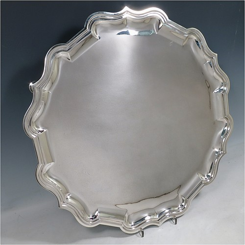 A large Antique Sterling Silver salver, having a round body, with a plain burnished ground, an applied Bath border, and sitting on four cast hoof feet. Made by Carrington and Co., of London in 1915. The dimensions of this fine hand-made antique silver salver are diameter 46 cms (18 inches), and it weighs approx. 2,388g (77 troy ounces).