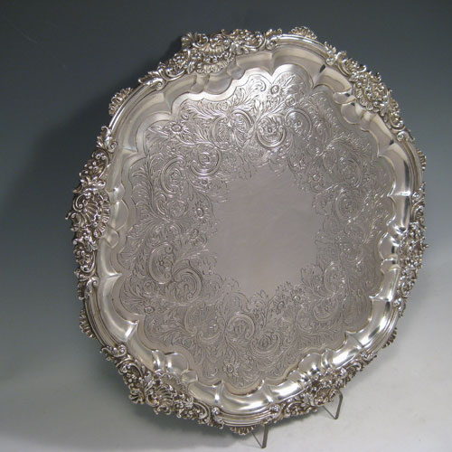 Antique Victorian sterling silver large table salver, having a hand-chased ground with floral and scroll decoration, a cast shell scroll and floral border, and sitting on three cast shell and scroll feet. Made by the Barnard Brothers of London in 1838. Diameter 41 cms (16 inches), height 4.5 cms (1.75 inches). Weight approx. 1,838g (59.3 troy ounces).