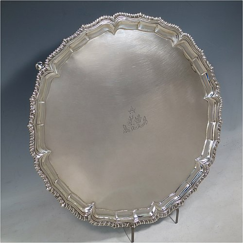 An Antique Georgian Irish Sterling Silver salver, having an applied shaped gadroon, a plain ground with a hand-engraved armorial central crest and Latin motto, and sitting on four cast hoof feet. Made in Dublin, Ireland, in 1796. The dimensions of this fine hand-made antique silver salver are diameter 36 cms (14.25 inches), and it weighs approx. 1,190g (38 troy ounces).