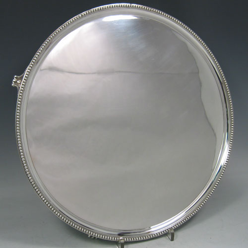 Antique Georgian sterling silver salver, having an applied bead border, plain ground, and sitting on four flange feet with bead edges. Made by Elizabeth Jones of London in 1790. Diameter 36 cms (14 inches). Weight approx. 1,248g (40.3 troy ounces).