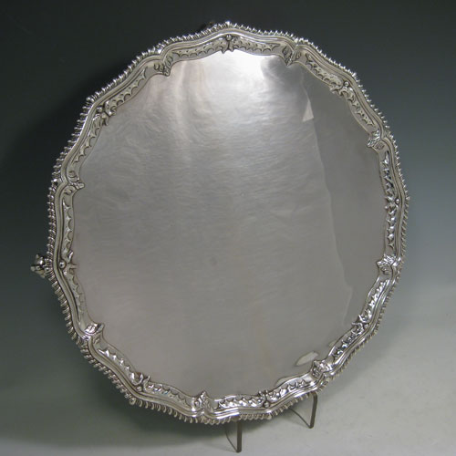 Antique Georgian sterling silver salver, having an applied shaped gadroon border with hand-chased anthemion leaves, a plain ground, and sitting on four cast claw and ball feet. Made by Richard Rugg of London in 1768. Diameter 38 cms (15 inches). Weight approx. 1,368g (44 troy ounces).