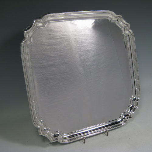 Sterling silver salver, having cut-corners with reeded borders, a plain ground, and sitting on four cast flange feet. Made by William Hutton and Sons of Sheffield in 1944. Dimensions 30 cms (12 inches) square. Weight approx. 1,082g (35 troy ounces).