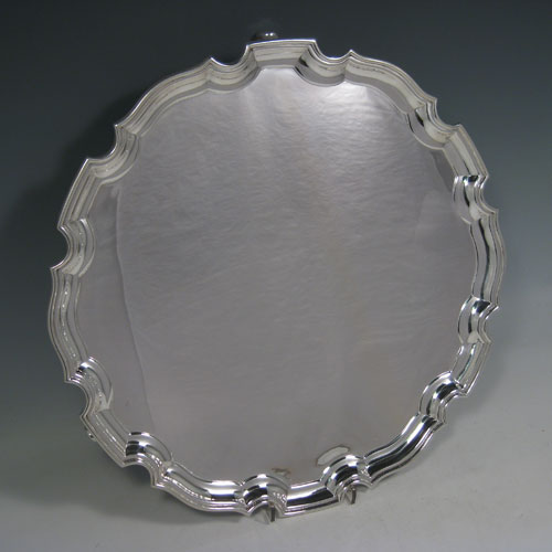 Sterling silver large salver, having a Chippendale border, plain ground, and sitting on three cast scroll feet. Made by the Adie Brothers of Birmingham in 1927. Diameter 36 cms (14 inches). Weight approx. 1,270g (41 troy ounces).