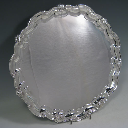 Sterling silver large salver, having a lobed and shell border, plain ground, and sitting on four cast foliate feet. Made by James Dixon and Sons of Sheffield in 1924. Diameter 36 cms (14 inches). Weight approx. 1,210g (39 troy ounces).