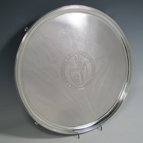 Antique Georgian sterling silver salver, having an applied reeded border, a plain ground with a hand-engraved armorial central crest, and sitting on four cast reeded feet. Made by Thomas Wallis II of London in 1796. The dimensions of this fine hand-made silver salver are diameter 33 cms (13 inches), and it weighs approx. 1,062g (34.3 troy ounces).