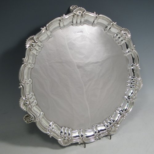A Sterling silver salver, having a round body, with a plain burnished ground, an applied Shell & Scroll  border, and sitting on three shell feet. Made by Walker and Hall of Sheffield in 1919. The dimensions of this fine hand-made silver salver are diameter 31 cms (12 inches), and it weighs approx. 658g (21 troy ounces).