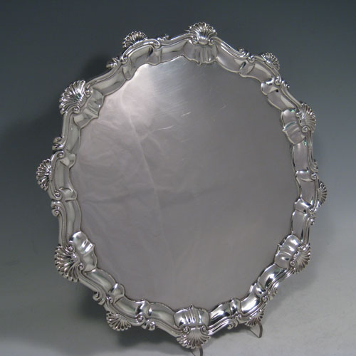 Antique Georgian sterling silver salver, having a shell and scroll border, a plain ground, and sitting on three cast hoof feet. Made by Ebenezer Coker of London in 1768. The dimensions of this fine hand-made silver salver are diameter 29 cms (11.5 inches), and it weighs approx. 688g (22 troy ounces).