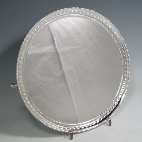 Sterling silver salver, having a round body, with a plain burnished ground, an applied double bead-edged border with a hand-chased garland of flowers, and sitting on three cast claw & ball feet. Made by William Hutton of Sheffield in 1931. The dimensions of this fine hand-made silver salver are diameter 25 cms (10 inches), and it weighs approx. 523g (17 troy ounces).
