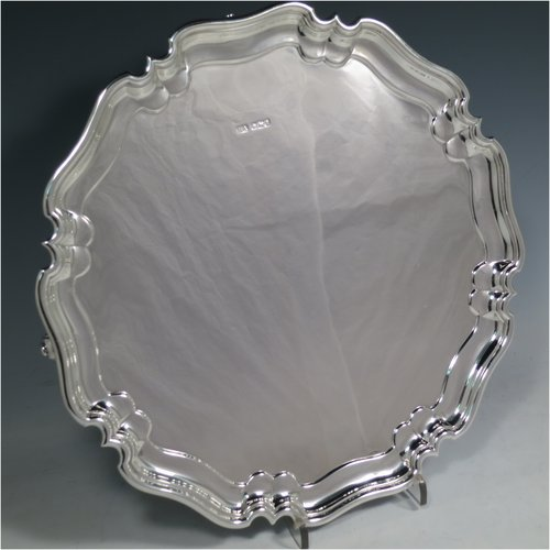 A Sterling Silver salver, having a round body, with a plain burnished ground, an applied Chippendale border, and sitting on four cast scroll feet. Made by Henry Atkins of Sheffield in 1917. The dimensions of this fine hand-made silver salver are diameter 32 cms (12.5 inches), and it weighs approx. 853g (27.5 troy ounces).