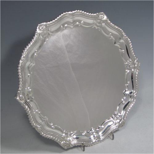 A Sterling silver salver, having a round body, with a plain burnished ground, an applied Shell & Shaped Gadroon border with scroll-work, and sitting on three cast claw & ball feet. Made by the Hardy Brothers of Sheffield in 1935. The dimensions of this fine hand-made silver salver are diameter 27 cms (10.5 inches), and it weighs approx. 626g (20 troy ounces).