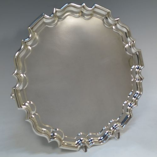 A very handsome and heavy Sterling Silver salver, having a round body, with a plain burnished ground, an applied Chippendale border, and sitting on three cast scroll feet. Made by Richard Woodman Burbridge (for Harrods) of London in 1938. The dimensions of this fine hand-made silver salver are diameter 30.5 cms (12 inches), and it weighs approx. 977g (31.5 troy ounces).