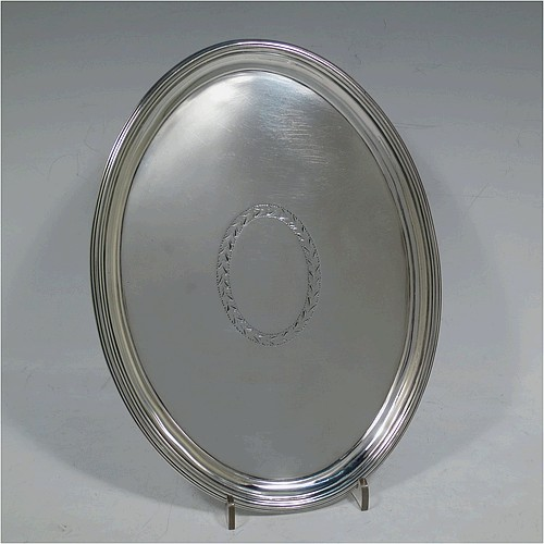 A very handsome Antique Georgian Sterling Silver George III oval salver, having a plain burnished ground with an oval vacant cartouche, an applied reeded border, and sitting on four cast flange feet. Made by George Smith and Thomas Hayter of London in 1802. The dimensions of this fine hand-made antique silver salver are length 23.5 cms (9.25 inches), width 18 cms (7 inches), and it weighs approx. 360g (11.6 troy ounces).