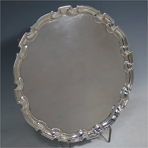 An Antique Georgian Sterling Silver George II salver, having a Chippendale border, a plain ground, and sitting on four cast scroll feet. Made by John Tuite of London in 1730. The dimensions of this fine hand-made antique silver salver are diameter 26.5 cms (10.25 inches), and it weighs approx. 491g (15.8 troy ounces).
