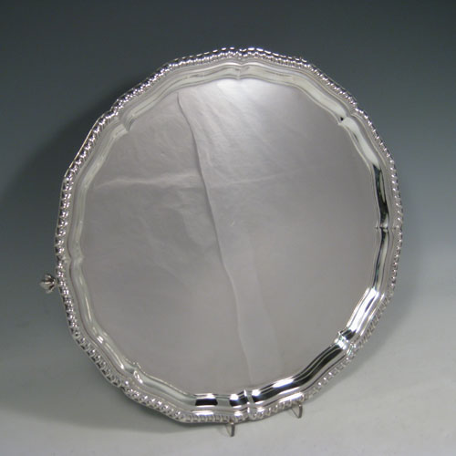 Sterling silver salver, having a shaped gadroon border, plain ground, and sitting on four cast claw and ball feet. Made by Charles Boyton and Sons of Sheffield in 1938. The dimensions of this fine hand-made silver salver are diameter 32 cms (12.5 inches), and it weighs approx. 958g (31 troy ounces).