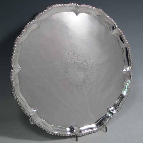 Antique Georgian sterling silver salver, having a shaped gadroon border, a plain ground with a centrally engraved armorial crest, and sitting on three cast hoof feet. Made by Richard Rugg of London in 1773. The dimensions of this fine hand-made silver salver are diameter 27.5 cms (10.75 inches), and it weighs approx. 685g (22 troy ounces).