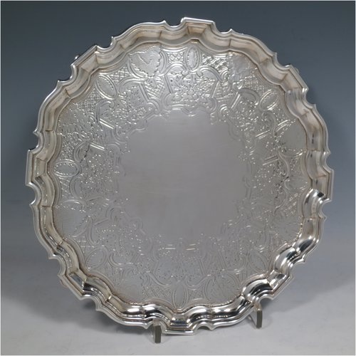 An Antique Georgian Sterling Silver salver, having an applied Chippendale border, a hand-chased ground with floral decoration, and sitting on four cast hoof feet. Made by George Hindmarsh of London in 1738. The dimensions of this fine hand-made silver salver are diameter 25 cms (10 inches), and it weighs approx. 594g (19.2 troy ounces).