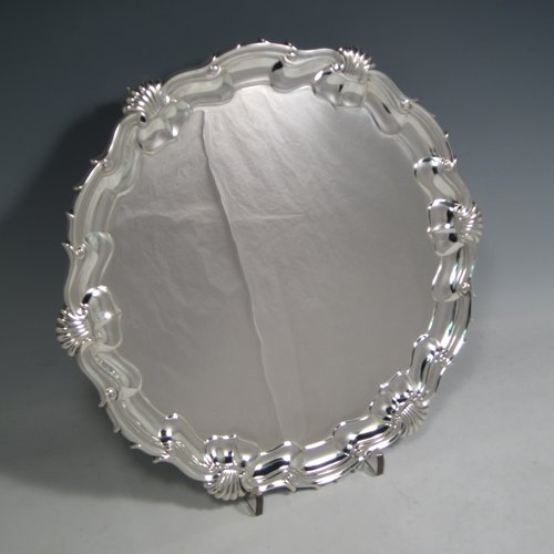 An Antique Edwardian Sterling silver salver, having a round body, with a plain burnished ground, an applied Shell & Scroll border, and sitting on three cast scroll feet. Made by W. G. Sissons of London in 1906. The dimensions of this fine hand-made silver salver are diameter 31 cms (12 inches), and it weighs approx. 822g (26.5 troy ounces).