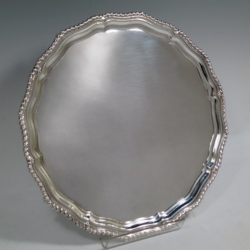 A very handsome Sterling Silver salver, having a round body, with a plain burnished ground, an applied shaped gadroon border, and sitting on four cast claw and ball feet. Made by the Barker Brothers of Birmingham in 1937. The dimensions of this fine hand-made silver salver are diameter 31 cms (12.25 inches), and it weighs approx. 1,040g (33.5 troy ounces).