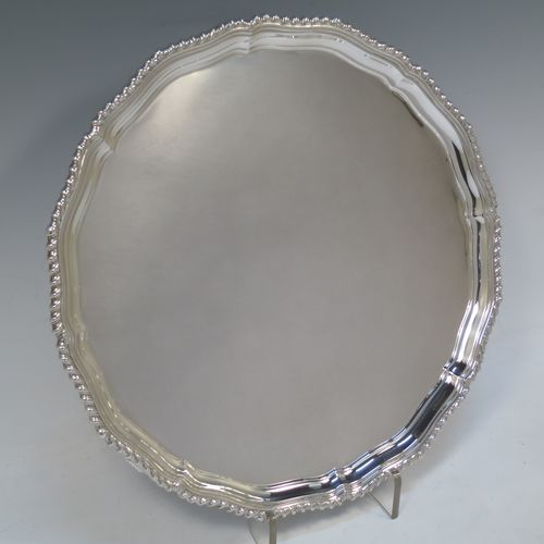 A very handsome Sterling Silver salver, having an applied shaped gadroon border, a plain ground, and sitting on three cast scroll feet. Made by I.S. Greenberg of Birmingham in 1929. The dimensions of this fine hand-made silver salver are diameter 30.5 cms (12 inches), and it weighs approx. 990g (32 troy ounces).