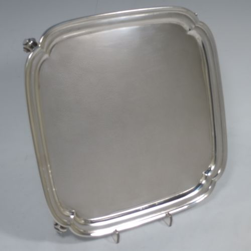A handsome Sterling Silver salver, having a square body with shaped and cut corners, a plain burnished ground, an applied reeded border, and sitting on four cast scroll feet. Made by S. Blanckensee and Sons of Birmingham in 1934. The dimensions of this fine hand-made silver salver are 23 cms (9 inches) square, and it weighs approx. 550g (17.7 troy ounces).