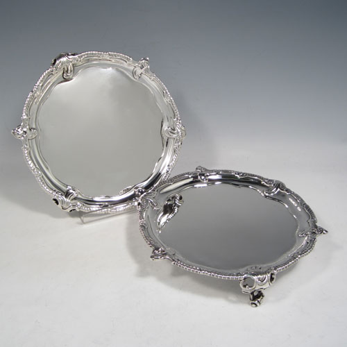 Antique Georgian sterling silver pair of George III salvers, having plain grounds, cast applied shaped gadroon and floral borders, and sitting on three cast and pierced foliate feet. Made by John Harvery I (possibly) of London in 1763 <a href=http://en.wikipedia.org/wiki/1763>(see what happened in this year).</a> The dimensions of these fine hand-made silver salvers are diameter 21 cms (8.25 inches), and they weigh approx. 789g (25.5 troy ounces).