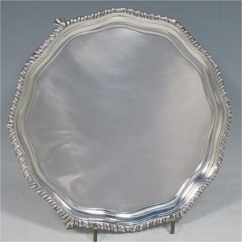An Antique Victorian Sterling Silver salver, having a shaped gadroon border, a plain ground, and sitting on three cast claw and ball feet. Made by Thomas Edward Harwood of London in 1877. The dimensions of this fine hand-made silver salver are diameter 19 cms (7.5 inches), and it weighs approx. 295g (9.5 troy ounces).
