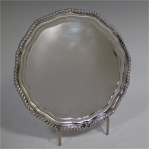 A very handsome Sterling Silver salver, having an applied shaped gadroon border, a plain ground, and sitting on three cast flanged feet. Made by Martin Hall and Co. Ltd., of Sheffield in 1924. The dimensions of this fine hand-made silver salver are diameter 21 cms (8.25 inches), and it weighs approx. 381g (12.3 troy ounces).