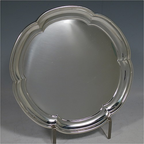 A Sterling Silver very handsome salver, having an applied scalloped edge border, a plain ground, and sitting on three flange feet. Made by the Henry Atkins of Sheffield in 1942. The dimensions of this fine hand-made silver salver are diameter 20 cms (8 inches), and it weighs approx. 340g (11 troy ounces).