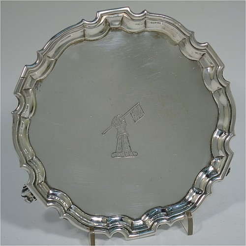An Antique Georgian Sterling Silver George II round salver, having a plain burnished ground, an applied Chippendale border, and sitting on three cast scroll feet. Made by Denis Langton of London in 1735. The dimensions of this fine hand-made antique silver salver are diameter 15.5 cms (6 inches), and it weighs approx. 186g (6 troy ounces). Please note that this salver is crested.