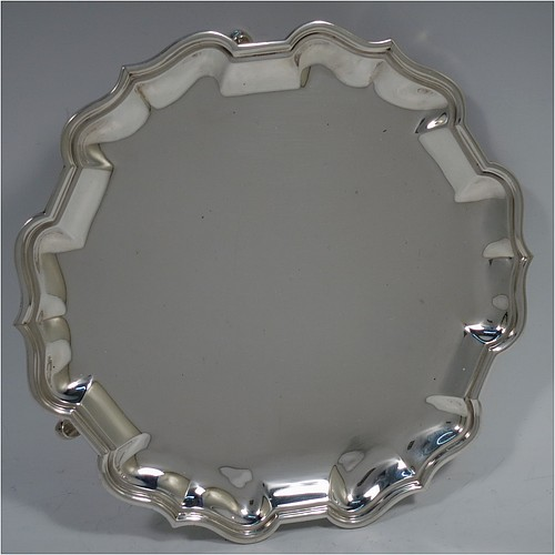 A classical Antique Sterling Silver round salver, having a plain burnished ground, an applied Chippendale border, and sitting on three cast hoof feet. Made by Hamilton and Co., of London in 1911. The dimensions of this fine hand-made antique silver salver are diameter 18 cms (7 inches), and it weighs approx. 250g (8 troy ounces).