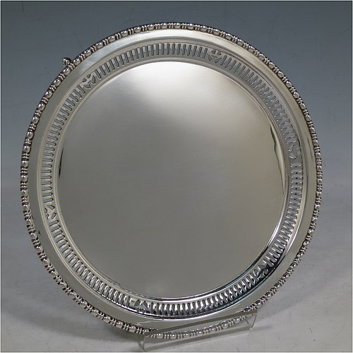 An Antique Sterling Silver salver, having a plain ground, with an applied egg & dart border above a band of hand-pierced geometrical decoration, and all sitting on three cast and scroll feet. Made by the Barker Brothers of Chester in 1911. The dimensions of this fine hand-made antique silver salver are diameter 20 cms (8 inches), and it weighs approx. 340g (11 troy ounces).