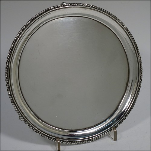 An Antique Georgian Sterling Silver salver, having a round body with a plain ground, an applied gadroon border, and all sitting on three fluted flanged feet. Made by Peter and William Bateman of London in 1809. The dimensions of this fine hand-made antique silver salver are diameter 16 cms (6.25 inches), and it weighs approx. 187g (6 troy ounces).