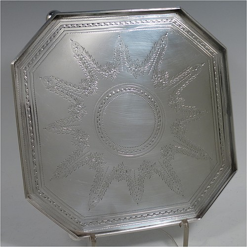 A very handsome and unusual Antique Victorian Sterling silver salver, having an octagonal body, a hand-engraved ground with floral swags and bands of bright-cut decoration, an applied reeded gallery border, and sitting on three cast cushion ball feet. Made by the Barnard Brothers of London in 1897. The dimensions of this fine hand-made antique salver are 21 cms (8.25 inches) square, height 2.5 cms (1 inch), and it weighs approx. 574g (18.5 troy ounces).