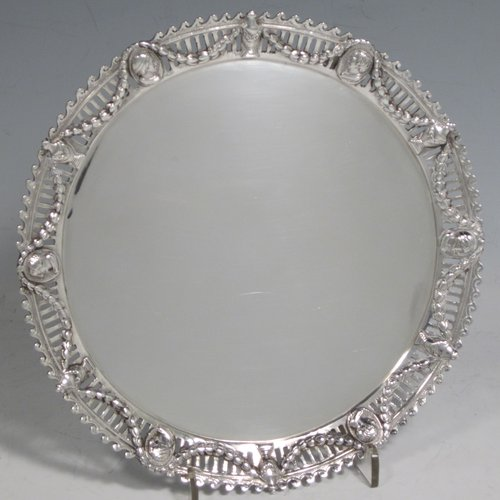 Antique Victorian sterling silver salver, having a plain ground, with an applied hand-chased and pierced border with neoclassical design showing swags, urns, portraits, and a wave-style border, and all sitting on three cast and scroll feet. Made by John Figg of London in 1873. The dimensions of this fine hand-made silver salver are diameter 18 cms (7 inches), and it weighs approx. 244g (7.8 troy ounces).