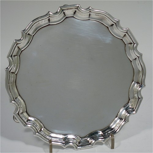 An Antique Georgian Sterling Silver George II round salver, having a plain burnished ground, an applied Chippendale border, and sitting on three cast hoof feet. Made by George Hindmarsh of London in 1736. The dimensions of this fine hand-made antique silver salver are diameter 15.5 cms (6 inches), and it weighs approx. 209g (6.7 troy ounces).