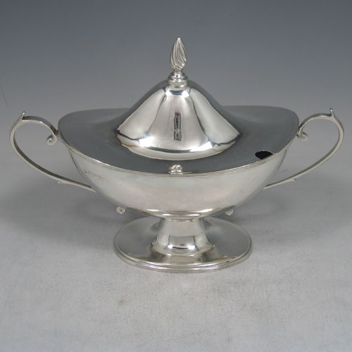 Antique Victorian sterling silver sauce tureen and cover, having a plain oval body, reeded borders, two scroll handles, a pull-off lid with flame finial, and all sitting on a pedestal foot. Made by Nathan and Hayes of Chester in 1901. Height 16 cms (6.25 inches), length 23 cms (9 inches), width 9 cms (3.5 inches). Weight approx. 360g (11.6 troy ounces).