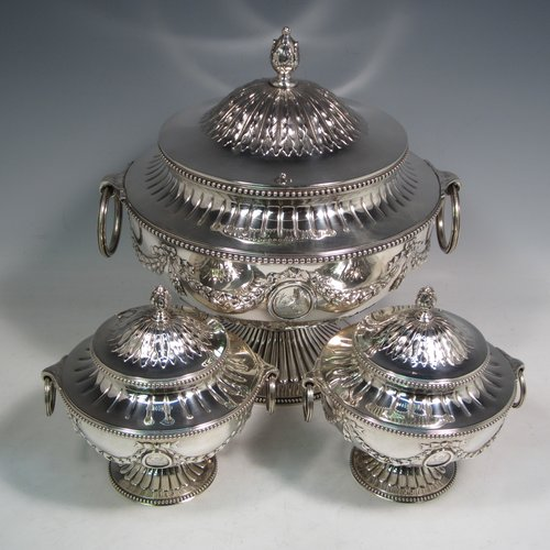 Antique Victorian sterling silver suite of soup and sauce tureens with covers, having round bodies with bead-edged borders, with hand-chased neoclassical style decoration, lift-off lids with anthemion leaves and cast floral finials, side  handles with attached rings, and all sitting on pedestal feet. Made by Robert Hennell II of London in 1872. The dimensions of the fine larger silver tureen are height 27 cms (10.5 inches), diameter length 23 cms (9 inches), with a total weight of approx. 2,356g (76 troy ounces). Please note that these items are crested in one cartouche.