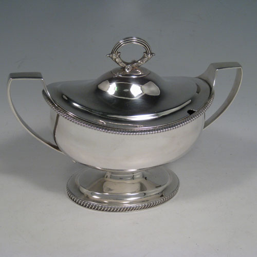 Antique Georgian George III sauce tureen, having an oval plain body, gadroon borders, lift off lid with asparagus loop handle and slot for sauce ladle, two side handles, and sitting on a pedestal foot. Made by Robert and Samuel Hennell of London in 1805. Length 21.5 cms (8.5 inches), width 11 cms (4.3 inches), height 18 cms (6.3 inches). Total weight approx. 545g (17.6 troy ounces).