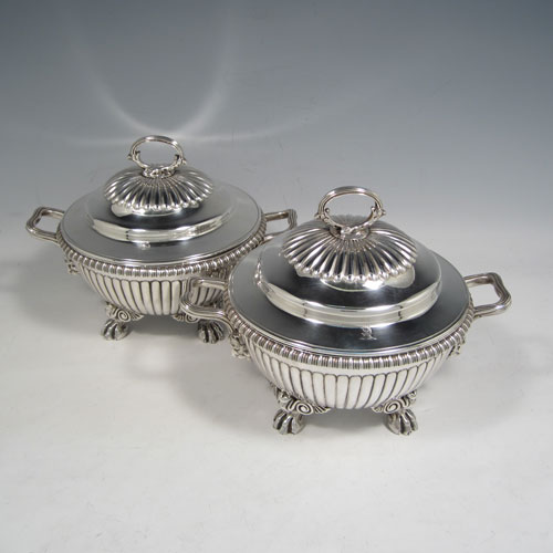 Antique Georgian sterling silver pair of sauce tureens, having round baluster bodies with hand-chased fluted decoration, lift-off lids with matching fluting and asparagus style loop handles, with reeded and lion-mask side-handles, and sitting on four cast lions-paw feet. Made by Emes and Barnard of London in 1810. The dimensions of these fine pair of hand-made silver sauce tureens are height 15 cms (6 inches), diameter 16 cms (6.25 inches), and they weigh a total of approx. 1,676g (54 troy ounces).