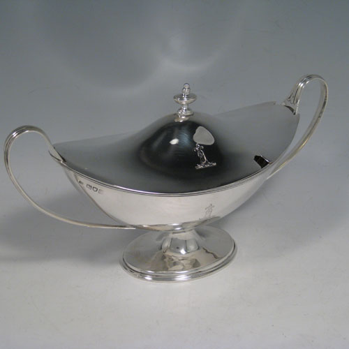 Antique Edwardian sterling silver sauce tureen, having a neoclassical boat-shaped body with reeded border, a lift-off cover with urn finial, two loop handles, all sitting on a pedestal foot. Made by Thomas Bradbury of London in 1904. Height 13 cms (5 inches), length 24 cms (9.5 inches), width 10 cms (4 inches). Total weight approx. 375g (12.1 troy ounces).