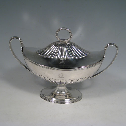 Antique Georgian sterling silver sauce tureen, having a neoclassical boat-shaped body with reeded borders and hand-chased half-fluted decoration, a lift-off cover with loop handle finial, all sitting on a pedestal foot. Made by Henry Chawner of London in 1795. Height 17 cms (6.75 inches), length 24 cms (9.5 inches), width 10 cms (4 inches). Total weight approx. 561g (18.1 troy ounces). Please note that this item is crested.