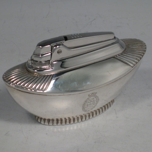 Sterling silver table lighter, having a plain oval lower body, with fluted shoulders, and sitting on a fluted collet foot. The lighter mechanism is by Ronson and is in fully working order. Length 11 cms (4.25 inches), height 6 cms (2.3 inches), width 4.5 cms (1.75 inches). Please note that this item is crested.